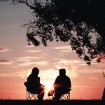 2 people sitting under a tree watching the sunset