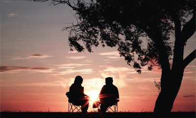 2 people sitting on chairs under a tree watching the sun set